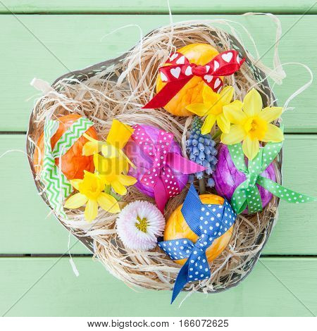 Easter basket with straw and colorful easter eggs