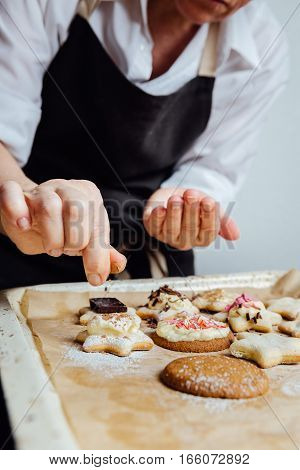 Person puts decorations on the top of the homemade cookies. Vertical studio shot.