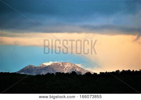 sunset reflecting on clouds in mountain with foreground cast in shadows