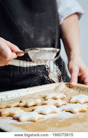 Hands of cook adding powdered sugar to cookies as a topping