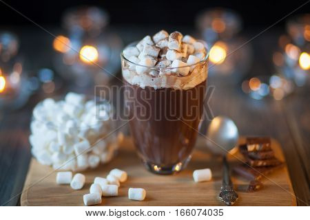 Beautiful composition - hot chocolate with marmalade and chocolate pieces in a transparent glass. The glass stands on a wooden stand. Behind the candles are burning. The composition rotates around its axis and beckons his appearance