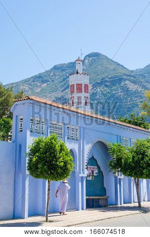 Arabic man standing in front of blue washed wall, red mosque and mountain in the town Chefchaouen, Morocco, North Africa.