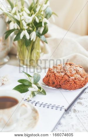 Cup of coffee open diary or notebook cookies and snowdrop flowers. Romantic breakfast.
