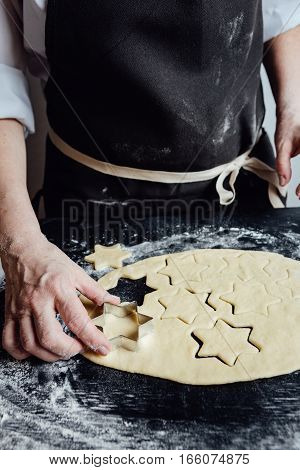 Hands of person making star-shaped cookies with metal form help.