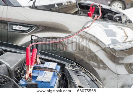Charging empty car battery with cables from another vehicle