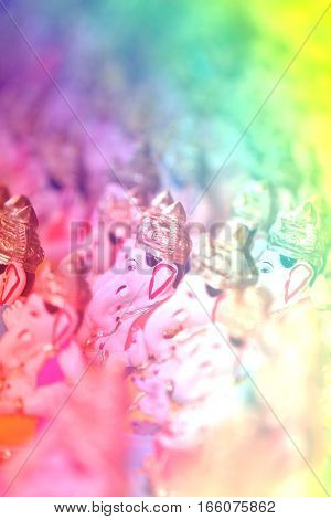 A beautiful view of Ganesh idols during Ganesh festival in India through a pastel curtain