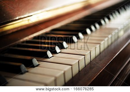Piano keyboard of an old music instrument close up with blurry background selective focus and very narrow depth of field