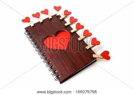 Notepad c wooden texture with red heart and clothespins on a white background.
