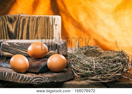 Raw eggs on various levels of wood boards near bird nest