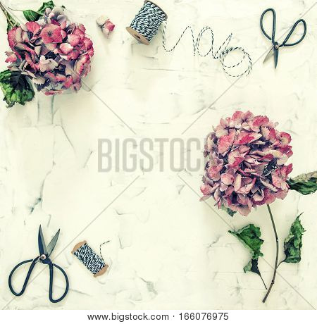 Flat lay with hortensia flowers and scissors on white marble background. Vintage style toned picture