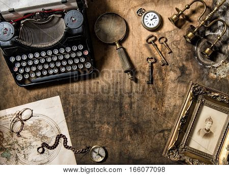 Vintage typewriter and old office accessories on wooden table. Nostalgic still life