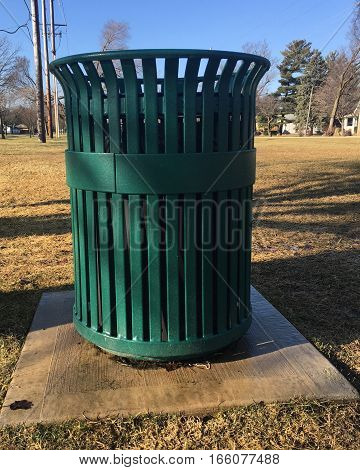 A green garbage can by a trail path.