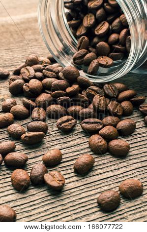 Coffee beans into glass jar on the wooden table. Closeup.