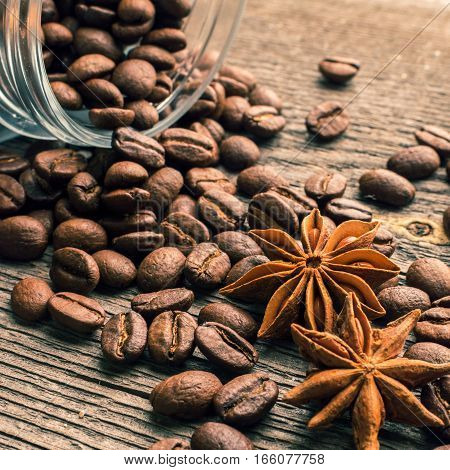 Coffee beans into glass jar table with csugar and anise on the wooden