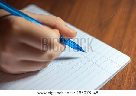 A close photo of a persons writing a letter with a pen.