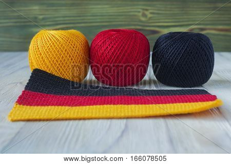 National Germany flag crocheted knitted pattern. Three balls of yarn in Germany flag colours