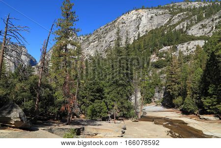 A lone hiker stops at the edge of Merced River as it flows towards Nevada Falls, Yosemite National Park, California.