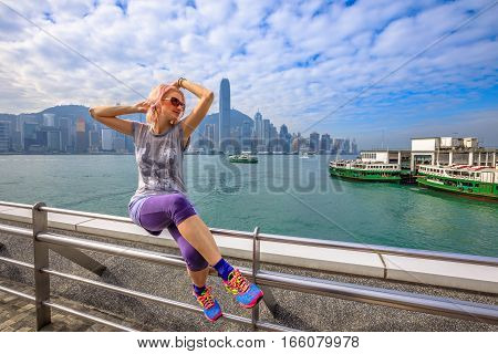 Caucasian woman with urban background Hong Kong skyline. Female fitness athlete after a workout outdoors on Tsim Sha Tsui Promenade in Victoria Harbour, Kowloon. Living healthy lifestyle concept.