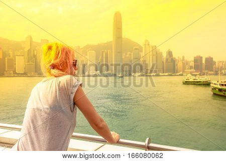 Travel asia concept. Tourists enjoying view and sightseeing on Victoria Harbour at sunset. Caucasian woman looking urban Hong Kong skyline from Tsim Sha Tsui Promenade, Kowloon. Travel tourism concept poster