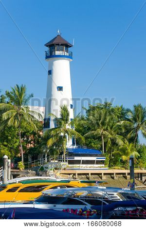 White lighthouse among palm trees in a tropical port