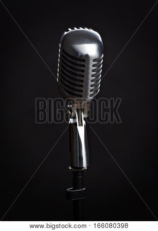 Silver metal vintage microphone on black background.