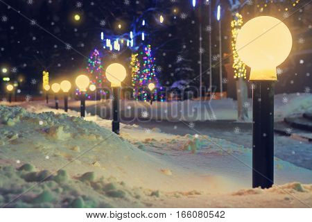 Lanterns in the night city winter. Falling snow sparkles of light of lanterns. Night landscape. Winter background with snowflakes.