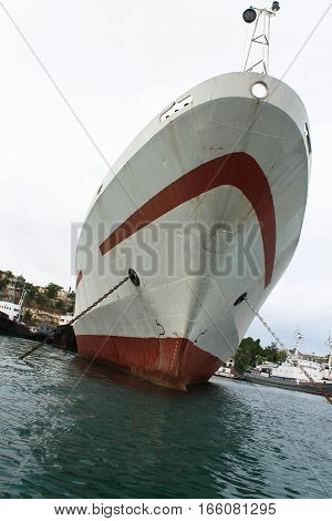 white ship with a red stripe is in a port