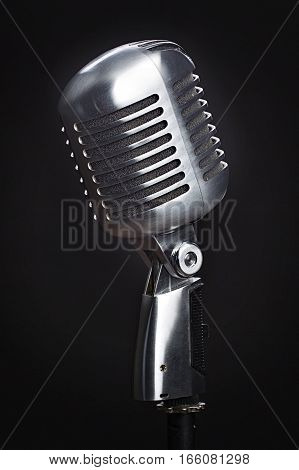 A vintage microphone on a black background