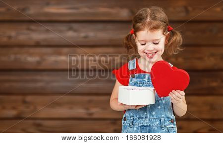 happy laughing child girl with gift Valentine's Day wooden background