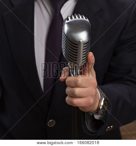 Man holding a retro microphone over black background.