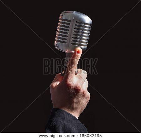 hand holding a retro microphone over black background.