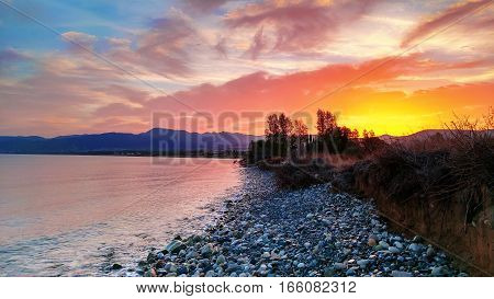Beautiful colorful sunrise at the sea with dramatic clouds and seashore with boulders