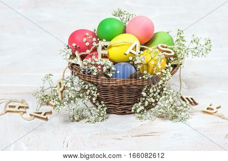 Easter eggs with flowers over bright wooden background. Festive decoration