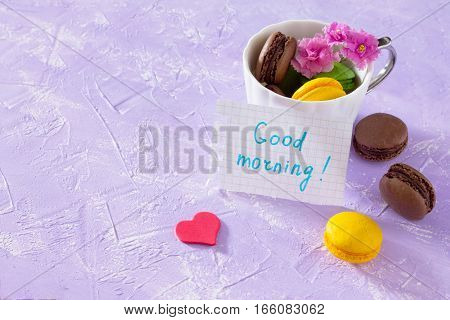 Mug Cakes Macaron, Leaf Notebook Inscription Good Morning On Purple Table Top. The Cozy Breakfast. C