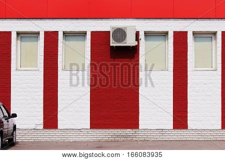 texture of bright red brick wall with white stripes, air conditioner and windows on a sunny day