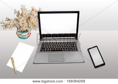 Work place with laptop white screen, smart phone, white blank paper and pen isolated.