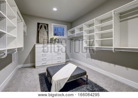 Huge Walk-in Closet With Shelves, Drawers And Gray Bench.