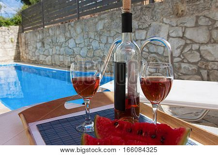 2 glasses and bottle of wine at poolside romance