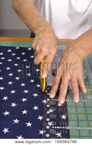 A quilter cuts fabric with a rotary cutter for use in a colorful quilt