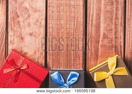 Colorful gift boxes on dark wood background with free space.
