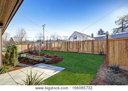 Sloped Backyard Surrounded By Wooden Fence Luxury New Construction Home With Open Floor Plan