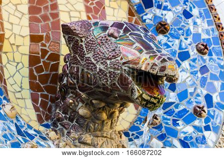Barcelona, Spain - September 20, 2014: Head of dragon ahead of coat of arms of Catalonia. Park Guell, Barcelona, Spain.