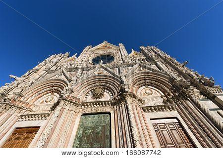 Facade of Siena Cathedral (Santa Maria Assunta) 1220-1370 with clear blue sky. Toscana (Tuscany) Italy Europe