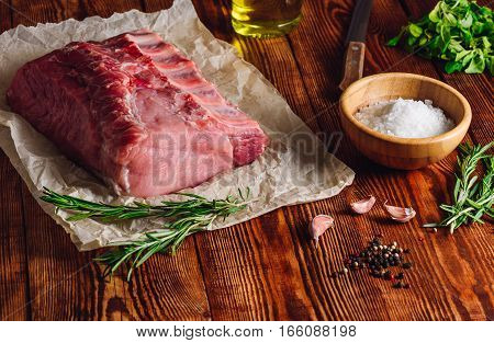 Raw Pork Loin with Ribs and Some Ingredients for Roasting