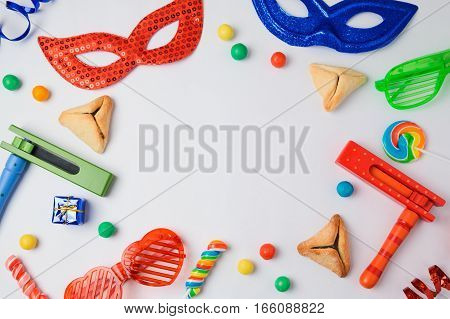 Jewish holiday Purim concept with hamantaschen cookies carnival mask and noisemaker on white background. View from above
