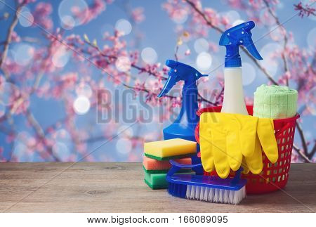 Spring cleaning concept with supplies over floral background