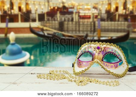 Carnival mask over blurred Venetian water background