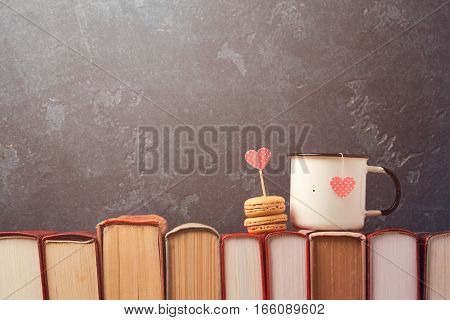 Valentines day concept with retro tea cup and macarons dessert on books over blackboard background