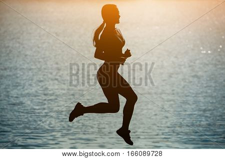 Silhouette of a beautiful athletic woman jumping during sports near the river at sunset. The concept of a healthy lifestyle.
