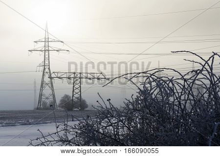 Electricity Pylons From Distribution Power Station In Foggy Winter Freeze